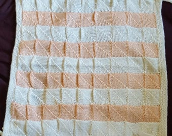 Knit baby cot blanket in peach and white