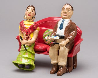 Ceramic, clay sculpture of Diego Rivera and Frida Kahlo sitting of sofa with paint brushes and paint palet. All in miniature.