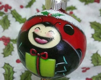This little ladybug is waiting to bring you a gift for Christmas day with a happy smile on her face.