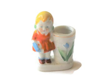 Vintage toothpick holder with yellow-haired girl in orange dress and blue purse. Occupied Japan collectible, cottage décor