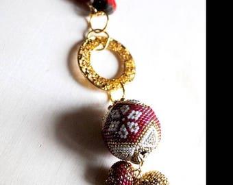 Sautoir boules perlées tissées rouge et or