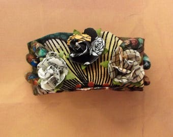 Fabric bracelet, earth tones, embellished with striking beads and 3 cloth flowers. Snap closure.