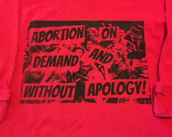 "Red prochoice feminist ""abortion on demand and without apology"" sweater. 20% of sales benefit national network of abortion funds"