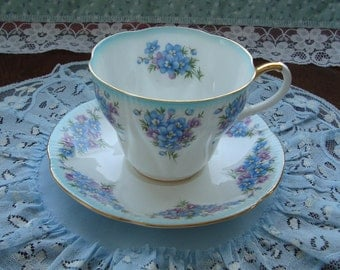 "Royal Albert Dainty Dina Series ""Emily"" - Bone China England - Tea Cup and Saucer - Shelley Shape with Blue and Purple Flowers, Blue Trim"