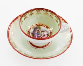 Small portrait-demitasse: pale-green/red ft. an Angelica Kaufmann-transfer, partly hand-decorated, goldcolor, 1925s