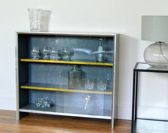 1970's vintage cabinet with glass doors. Re-Designed in Grey with Gold and Silver leaf details. Drinks cabinet, book case.