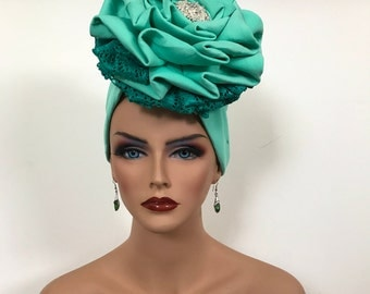 A mint Green hat with lacy design and bead
