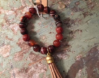 Rust beaded bracelet with gold tassel
