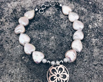 White iridiscent natural freshwater pearl bracelet feauturin a beautiful rose gold flower charm