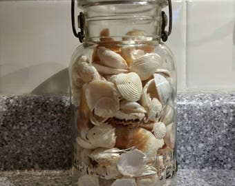 Vintage ball quart canning jar with glass lid.  Filled with seashells.