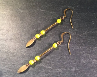 Long earrings with neon yellow beads.