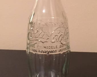 Cute, mini Coca-Cola bottle, with French writing on the sides.