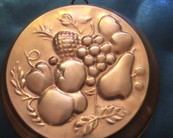 Vintage round copper mold of fruit.