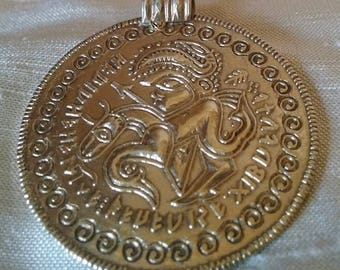 Bracteate pendant with horse and runic inscription. Museum copy.