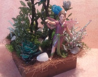 Miniature garden with fairy small blue and purple