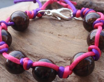 Fuchsia pink and purple cord and Brown hues beads black.