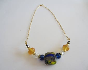 handmade Lampwork necklace with a large handcrafted blue and yellow glass bead and chain or gold - filed
