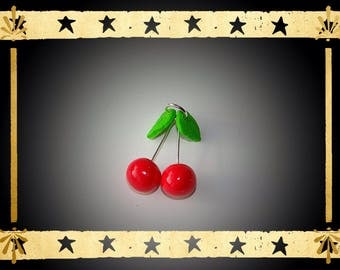 Bright red cherries with two lime green leaves