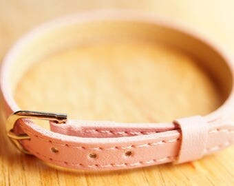 Pink faux leather padded strap.