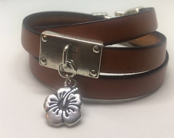 Leather wrap bracelet with hibiscus charm.