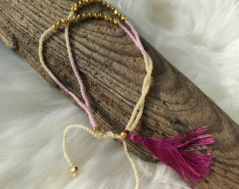 Cream and pink beaded friendship bracelet with gold accent beads and purple tassel