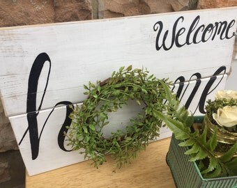 Welcome home sign with green wreath