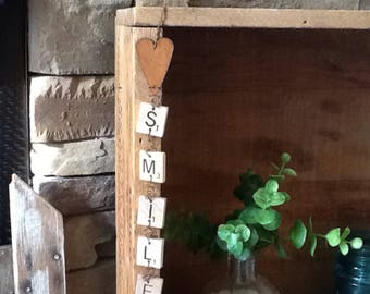 scrabble tiles and rusty wire smile sign