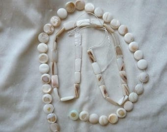 2 strands of Mother of Pearl, 1 natural bleached 10mm coin, and 1 natural bleached 14x8mm rectangle Beads on 15 inch Strands.