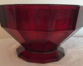 A large, heavy, vintage footed glass bowl in deep red.