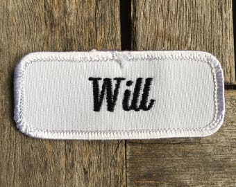 """Will. A white work shirt name patch that says """"Will"""" in black script"""