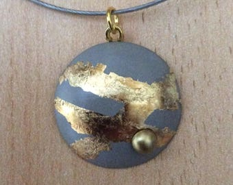 Pendant in concrete, around finished with gold leaf and a Pearl