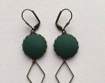 brass earrings and bottle green fabric