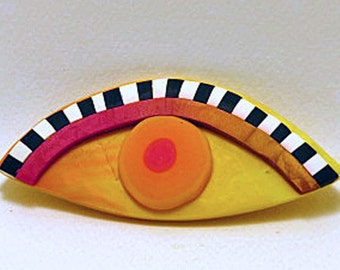 Brooch. Oval shaped eye brooch with black and white eyelashes. Fun one of a kind brooch. Yellow and orange eye shaped brooch.