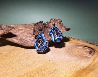 Blue vines n' things, random border design around dried seed pod mesh under glass. Hand sculpted and painted earrings.