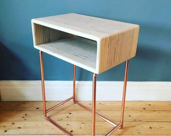 Side table in a modern industrial style with a copper pipe frame and birch plywood storage pod