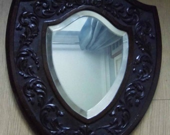 Victorian shield shaped wall hanging mirror with bevelled glass, encased carved shell