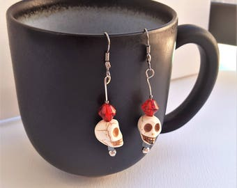 Bone colored skull dangle earrings with red beads and silver fittings