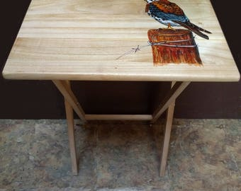 A set of four custom hand painted snack tables with storage rack