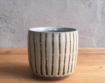 Wood fired yunomi with green glaze and brown stripes.