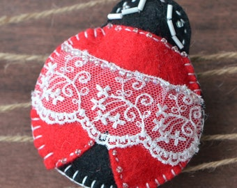 An Adorable Ladybug Brooch handmade with felt, beads and lace.