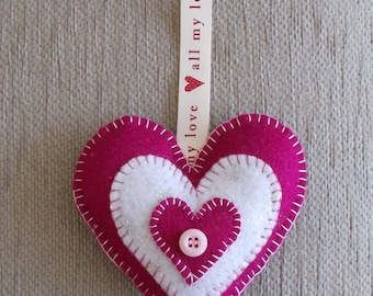 A handmade rose pink and white felt love heart hanging decoration