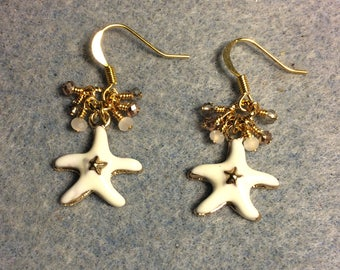 White and gold enamel starfish charm earrings adorned with tiny dangling white, gold, and clear Chinese crystal beads.