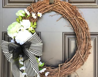 Rustic simple wreath with black and white linen bow, green and white Ranunculus flowers and small white accents
