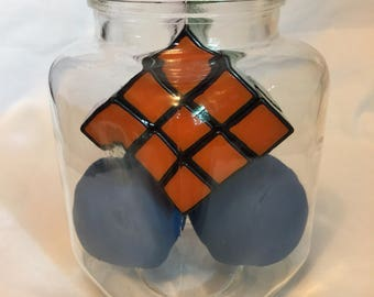 3x3 Rubiks cube and racquetballs in a jar without lid