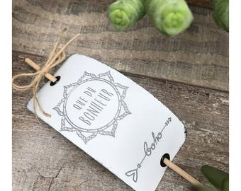 A pretty white metal tag with engraving * happiness that * on wooden stick