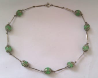 silver coloured necklace with capped green melon shaped glass beads
