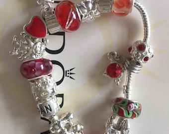 red pandora style bracelet, hallmarked 925 with pandora bag