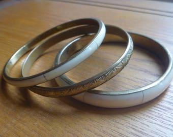 stacking bracelets, three brass and off-white enamel bracelets