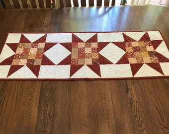 Quilted patchwork star table runner in shades of rust and tan