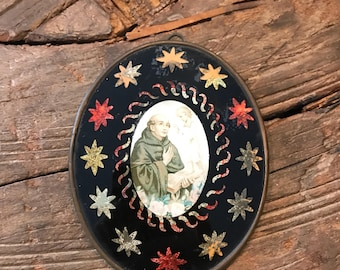 Vintage religious wall hanging showing Saint Anthony under glass with star and other cutouts with glittery foil underneath